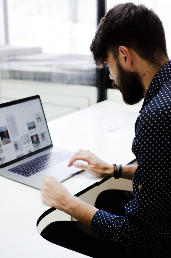 A man sits in front of a laptop for blog writing